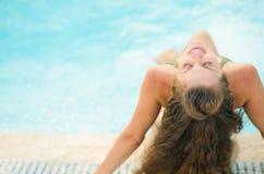 Glückliche junge Frau, die am Poolside sich entspannt. hintere Ansicht Stockfotos