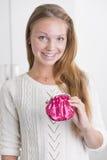 Glückliche junge Frau, die rosafarbenen Fonds anhält stockfotografie