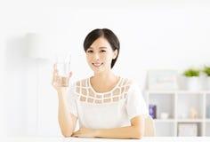 Glückliche junge Frau, die Süßwasser trinkt stockfoto