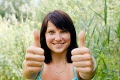 Glückliche junge Frau, die sich Daumen zeigt Stockfoto