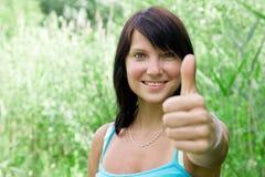 Glückliche junge Frau, die sich Daumen zeigt Stockbild
