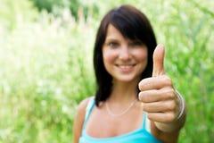 Glückliche junge Frau, die sich Daumen zeigt Lizenzfreie Stockfotografie