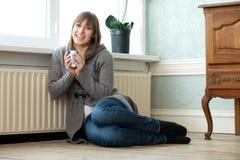 Glückliche junge Frau, die sich zu Hause mit einer Tasse Tee entspannt Stockfotos