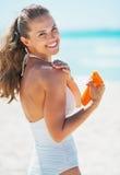 Glückliche junge Frau, die Sonnenblockcreme auf Strand anwendet Stockbild