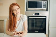 Glückliche junge Frau, die Tablette hält und Kamera betrachtet lizenzfreie stockfotos
