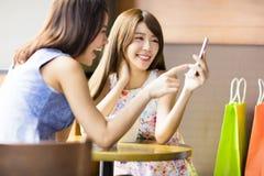Glückliche junge Frau, die Telefon in der Kaffeestube betrachtet Stockfotografie