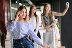 Glückliche junge Frau, die am Telefon im Einkaufszentrum spricht lizenzfreie stockfotos