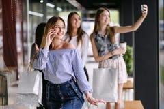 Glückliche junge Frau, die am Telefon im Einkaufszentrum spricht stockbild