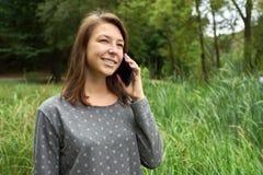 Glückliche junge Frau, die am Telefon im Wald spricht Stockbild