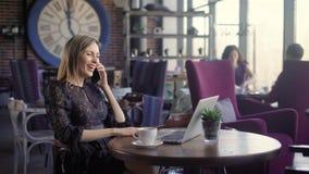 Glückliche junge Frau, die am Telefon spricht und Computer in einer Kaffeestube verwendet Ein schönes Mädchen, steht emotional in stock footage