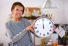Glückliche junge Frau, die Uhr im Weihnachten zeigt Lizenzfreie Stockbilder