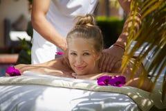 Glückliche junge Frau, die während der Massage im Badekurort lächelt Stockfotos