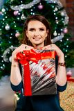 Glückliche junge Frau, die Weihnachtsgeschenk hält lizenzfreie stockfotografie