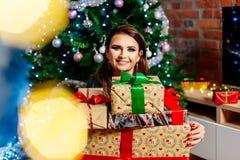 Glückliche junge Frau, die Weihnachtsgeschenk hält stockfotos