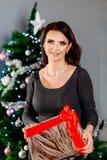 Glückliche junge Frau, die Weihnachtsgeschenk hält lizenzfreies stockbild