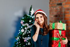 Glückliche junge Frau, die Weihnachtsgeschenk hält und einen Telefonanruf macht stockfotografie