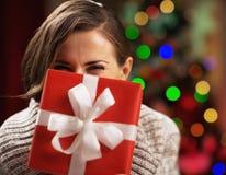 Glückliche junge Frau, die Weihnachtspräsentkarton vor Gesicht hält Stockfoto