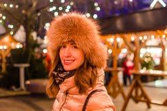 Glückliche junge Frau, die am Wintermarkt lächelt Stockfotos
