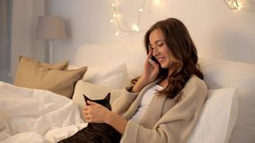Glückliche junge Frau, die zu Hause um Smartphone ersucht stock footage