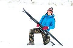Glückliche junge Frau draußen mit einem Paar Skis lizenzfreies stockbild