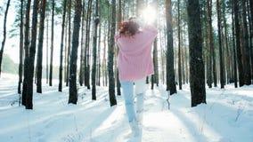 Glückliche junge Frau in einem Winterwald, laufend in den Schnee unter den Bäumen, Rücklicht macht seine Weise durch die Bäume stock footage