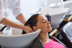 Glückliche junge Frau am Friseursalon Stockfotos