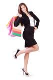 Glückliche junge Frau geht und trägt Taschen mit Käufen Stockbild