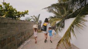 Glückliche junge Frau geht zusammen mit wenigen Jungen- und Mädchentragetaschen in Richtung zum Ozeanstrand entlang weniger Palme stock video footage