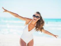 Glückliche junge Frau im Badeanzug, der Spaßzeit auf Strand hat Stockfoto