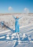 Glückliche junge Frau im blauen Skianzug auf Schnee lizenzfreie stockbilder