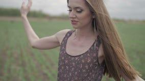 Glückliche junge Frau im dunklen Kleid mit Blumendruck stock footage