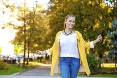 Glückliche junge Frau im gelben Mantel in der Herbststraße stockbild
