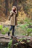Glückliche junge Frau im Herbstwald Stockfoto