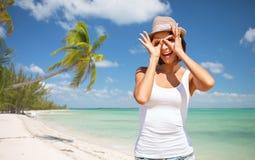 Glückliche junge Frau im Hut auf Sommerstrand Stockbild