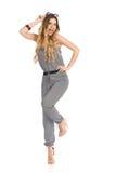 Glückliche junge Frau im Overall steht auf einem Bein und Blinzeln Stockfoto