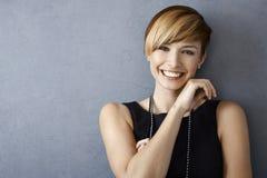Glückliche junge Frau im schwarzen Kleid und in den Perlen lizenzfreie stockbilder