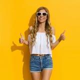 Glückliche junge Frau im Sonnenlicht gibt Thums auf Lizenzfreies Stockfoto