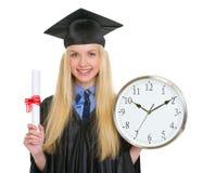 Frau im Staffelungskleid, das Diplom und Uhr hält Lizenzfreie Stockfotos