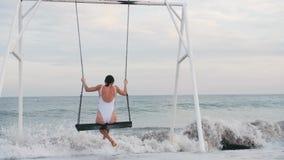 Glückliche junge Frau im weißen Badeanzugreiten auf Schwingen Seeansicht genießend Sch?ne junge Frau an einem Pool stock video