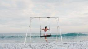 Glückliche junge Frau im weißen Badeanzugreiten auf Schwingen Seeansicht genießend Sch?ne junge Frau an einem Pool stock video footage