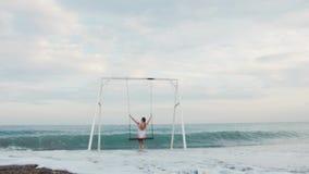 Glückliche junge Frau im weißen Badeanzugreiten auf Schwingen Seeansicht genießend Sch?ne junge Frau an einem Pool stock footage