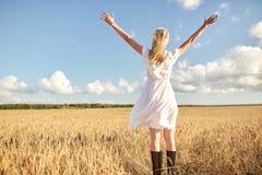 Glückliche junge Frau im weißen Kleid auf Getreidefeld stockfotos