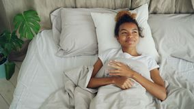 Glückliche junge Frau liegt im Bett, das wach ist und lächelt, sorgloses Leben, bequemes Bett und gute Nachrichten genießend posi stock video footage