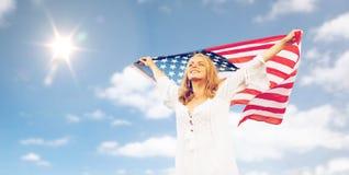 Glückliche junge Frau mit amerikanischer Flagge über blauem Himmel Lizenzfreie Stockbilder