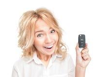 Glückliche junge Frau mit Autotaste auf Weiß. Stockfoto