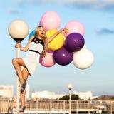 Glückliche junge Frau mit bunten Latexballonen Stockbild