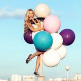 Glückliche junge Frau mit bunten Latexballonen Lizenzfreie Stockfotos