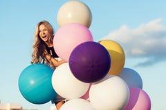 Glückliche junge Frau mit bunten Latexballonen Lizenzfreie Stockfotografie