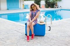 Glückliche junge Frau mit dem blauen Gepäck, das zum Erholungsort ankommt Sie geht nahe bei dem Swimmingpool Anfang von Stockfotos