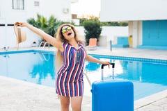 Glückliche junge Frau mit dem blauen Gepäck, das zum Erholungsort ankommt Sie geht nahe bei dem Swimmingpool Anfang von Stockfotografie